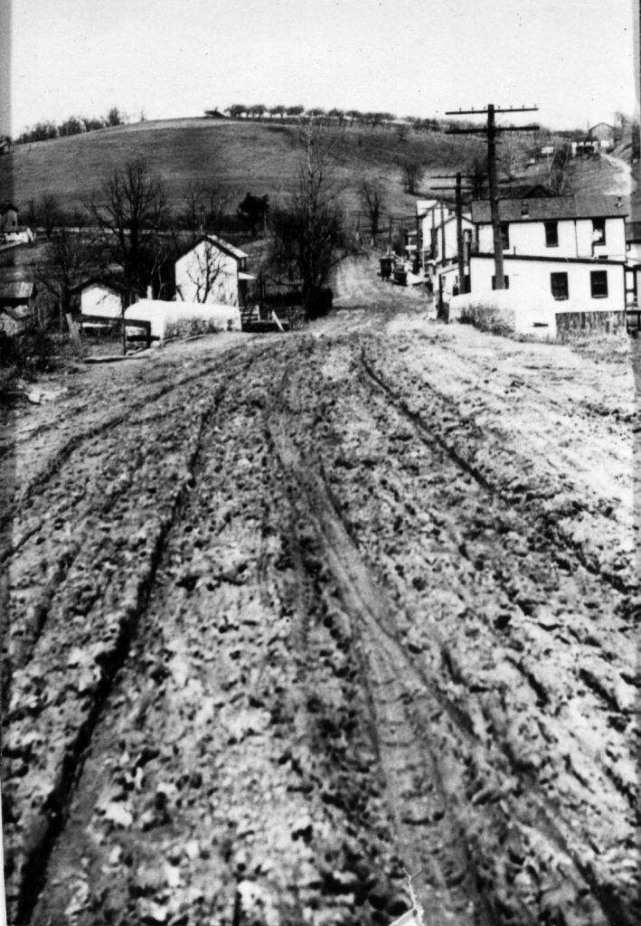 1920 Perry Highway, unpaved, rutted by wagon wheel tracks, view looking north through village of Pine Creek